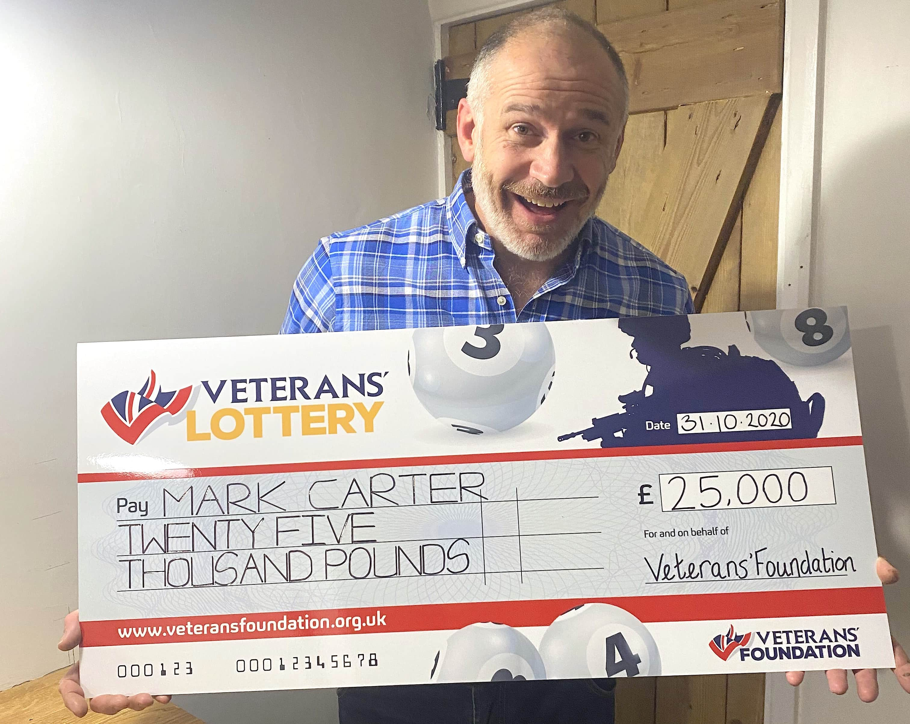 man holding cheque for £25,000